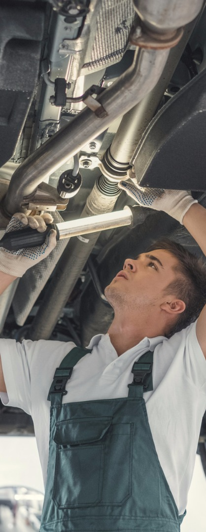 Mechanic Using Light To Check Underneath Car For Repairs